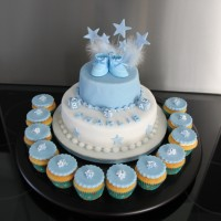 blue christening cake with blue shoes on top