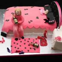 pink novelty cake - lady sat on a bed with wine